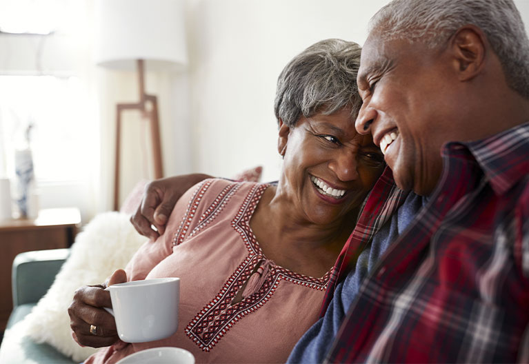 Elderly couple laughing and smiling.